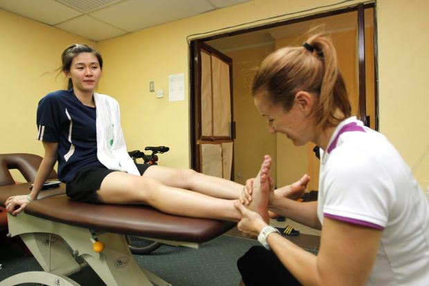 Woon Khe Wei getting some much needed attention from National Sports Institute physiotherapist Sandra Fiedler.