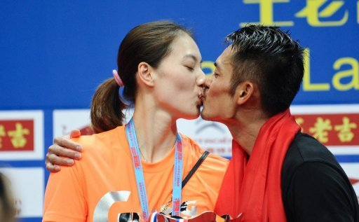 China's Lin Dan kisses his wife Xie Xingfang after winning his men's singles final on August 11, 2013
