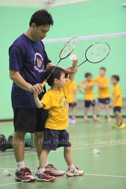 Coach is teaches kids serve Badminton at Intanon's badminton school